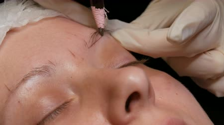 contorno : Beautician makes eyebrow shape correction to his patient. Marking the contour of the eyebrows with special pencil