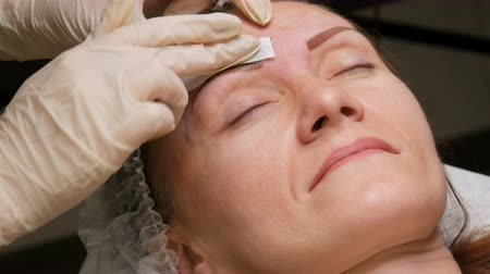 woman waxing : Eyebrow shape correction with wax. Green warm wax is applied to womans face to remove excess hair and eyebrows