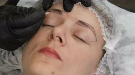 salon : Measure the shape of new eyebrows with special dyed thread. Microblading, permanent makeup, tattoo, Face contour