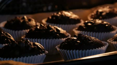 bread pan : Delicious chocolate muffins are cooked in the oven. Chocolate muffins in paper molds sprinkled with chocolate powder in form of cubes