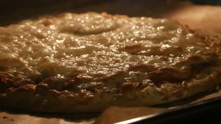taje : Big pizza is baked in oven. Cheese melts on pizza surface