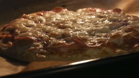 taje : Italian pizza is baked in oven at home. Cheese melts on pizza surface