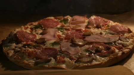 основное блюдо : Delicious pizza with mushrooms, salami, bacon, herbs, and cheese is cooked in oven