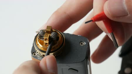 vaper : A man inserts new iron coil into a brown electronic cigarette Stock Footage