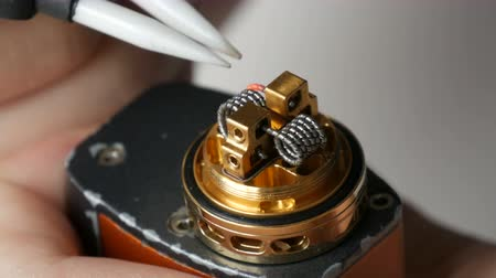 ayarlanabilir : A man inserts new iron coil into a brown electronic cigarette Stok Video