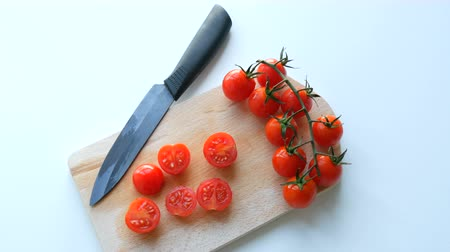 košíček : Stylish ceramic kitchen knife and ripe red small small cherry tomatoes in bunch of bunches and partially cut on the kitchen board Dostupné videozáznamy