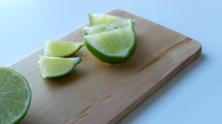 гарнир : Ripe green lime sliced on kitchen wooden board on a white table background