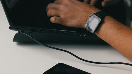 multi media : A man works at laptop. Mens hands with a smart watch and an electronic cigarette are typing on the keyboard.