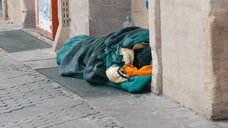 alms : Nuremberg, Germany - December 10, 2019: A homeless poor beggar lying on the ground in sleeping bag and asks for alms on a city street in winter Stock Footage