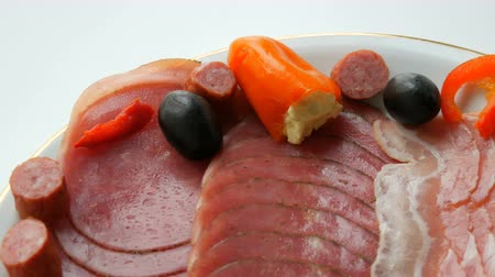 smoked : Meat and sausage slices on plate next to black olives, paprika with cheese and hunting sausages. Salami and sliced ham. Arranged dried meat in restaurant. Appetizing. Cured meat plate Stock Footage