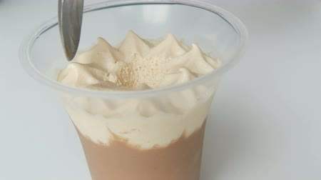 açoitado : Dessert of whipped cream and chocolate in plastic cup. Female hand with teaspoon removes the top of the cream Vídeos