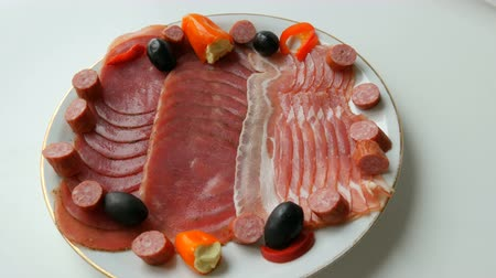 lardo : Meat and sausage slices on plate next to black olives, paprika with cheese and hunting sausages. Salami and sliced ham. Arranged dried meat in restaurant. Appetizing. Cured meat plate Filmati Stock