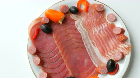 вылеченный : Meat and sausage slices on plate next to black olives, paprika with cheese and hunting sausages. Salami and sliced ham. Arranged dried meat in restaurant. Appetizing. Cured meat plate Стоковые видеозаписи