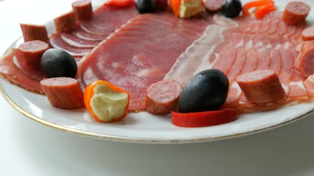 olivy : Meat and sausage slices on plate next to black olives, paprika with cheese and hunting sausages. Salami and sliced ham. Arranged dried meat in restaurant. Appetizing. Cured meat plate Dostupné videozáznamy