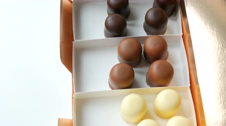 風通しの良い : A half-empty box with airy desserts of souffle Bizze in the form of sweets in glaze of white, black and milk chocolate. Box of chocolates on a white table