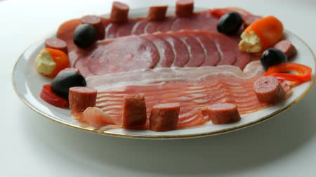 вылеченный : Meat and sausage slices on plate next to black olives, paprika with cheese and hunting sausages. Cured meat plate