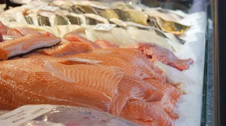 szervezett : Showcase of the fish store. Huge pieces of red fish in ice. Fillet of salmon and other marine fish for sale