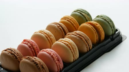 stapelen : Multicolored french cookies macaron in a special black box on a white table. Colorful cake macaroon in a gift box