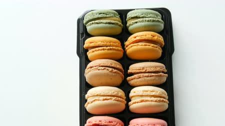 empilhamento : Multicolored french cookies macaron in a special black box on white table top view Vídeos