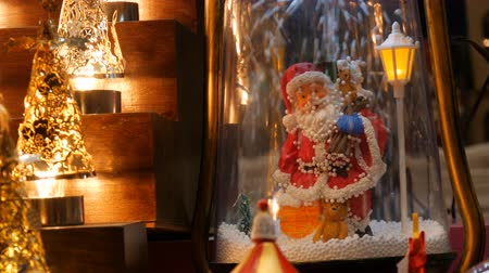 kaligrafia : Beautiful cozy luminous Christmas lights and Santa Claus figurine on which artificial snow falls on market counter