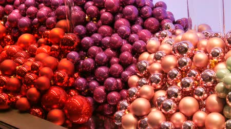 önemsiz şey : Large number of New Year and Christmas tree balls of pink, red, purple in the store window. Christmas decor Stok Video