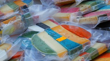 wooden type : Interesting multi-colored hard cow and goat cheese of various tastes at the grocery store on the market. Cheese yellow, red, lavender, black, green. Stock Footage