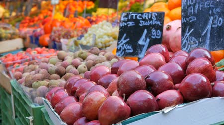 апельсины : Foreground are big red apples and exotic fruits. Vegetable market in a big city. Huge selection of various vegetables and fruits. Healthy fresh organic vegan food on the counter. Price tags in German Стоковые видеозаписи