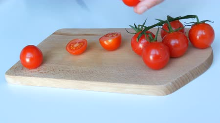 tomate cereja : Female hands cut beautiful juicy ripe red cherry tomatoes in branches on white table background and wooden kitchen board