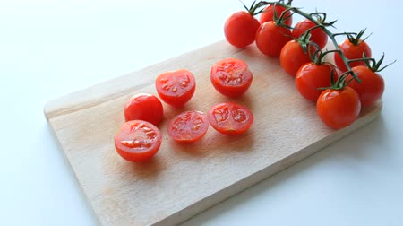košíček : Ripe red small cherry tomatoes in a bunch of clusters and partially cut on the kitchen board and white background