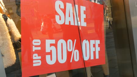 ikon : Red label with inscription sale in store, Season of sales and discounts. Big red label at store on display 50% off red label in modern city. Going shopping during seasonal sales.