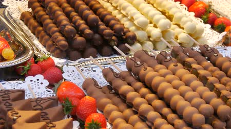 špejle : Various fruits on a wooden skewer stick in caramelized glaze made of milk black white chocolate. Grapes, banana, strawberries in icing on the counter of the Christmas market