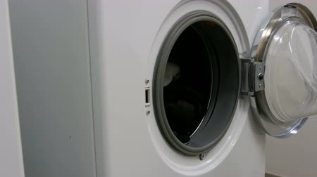 ev işi : Men hands loads laundry and clothes into washing machine. Large white washing machine in the laundry room. Stok Video