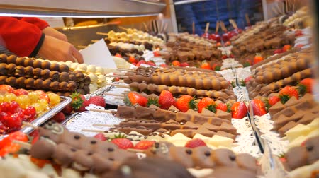покрытый : Various fruits on a wooden skewer stick in caramelized glaze made of milk black white chocolate. Grapes, banana, strawberries in icing on the counter of the Christmas market