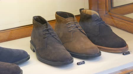 mindennapi : Stylish shoes made of suede leather on the window of a shoe store with price tags and discounts Stock mozgókép