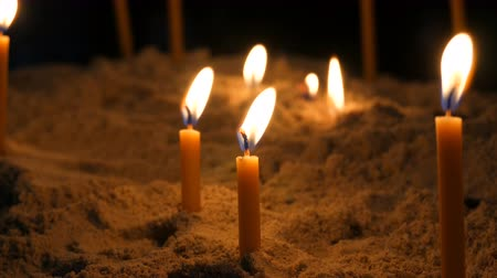 vasárnap : Long thin yellow church candles burn in sand Stock mozgókép