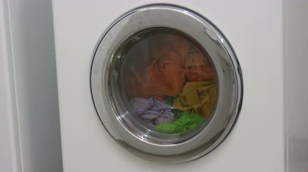 sem camisa : Multi-colored clothes laundry is washed in a white washing machine in the laundry room. Stock Footage