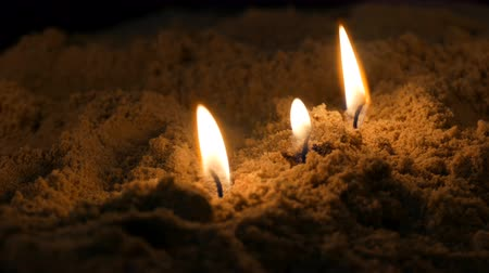 ortodoxia : Long thin yellow church candles burn in sand Stock Footage