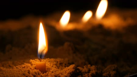 suporte : Long thin yellow church candles burn in sand Stock Footage