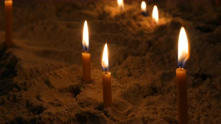 sobor : Long thin yellow church candles burn in sand Stock Footage