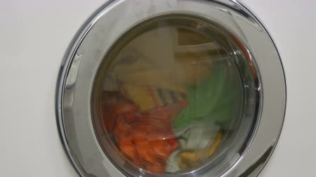 세탁기 : Multi-colored clothes laundry is washed in a white washing machine in the laundry room. 무비클립