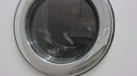 wasserij : Black and white clothes. Laundry is washed in a white washing machine in the laundry.