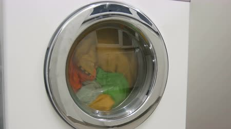 wasserij : Multi-colored clothes laundry is washed in a white washing machine in the laundry room. Stockvideo