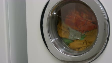 prát : Multi-colored clothes laundry is washed in a white washing machine in the laundry room. Dostupné videozáznamy