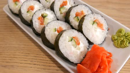 унаги : Large sushi rolls in a nori with salmon, crab sticks, cucumbers, philadelphia cheese. Nearby is green wasabi and red ginger. Japanese food