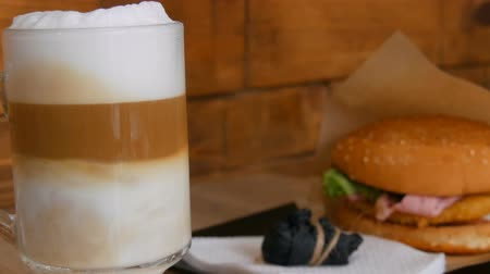 brew coffee : Delicious freshly made latte on a table in a cafe. Milk foam from latte coffee in transparent long special glass. In background is a delicious hamburger with lettuce, meat cutlet. Unhealthy fast food
