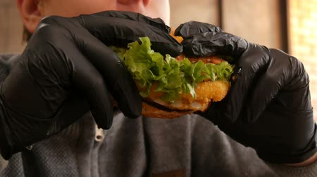 кунжут : Teenager boy in black rubber gloves is eating a burger. Delicious juicy fresh burger on the table in a fast food restaurant. Salad leaves, fresh bun, meat cutlet, unhealthy sauce
