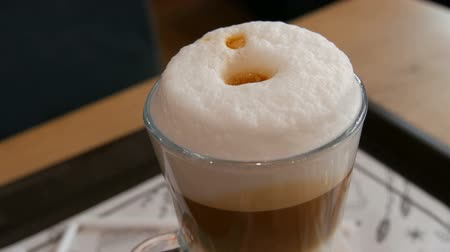 borrão : Delicious freshly made latte on a table in a cafe. Latte coffee milk foam in a transparent long special glass.