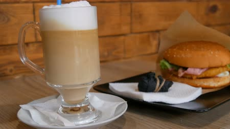 laktóz : Delicious freshly made latte on a table in a cafe. Milk foam from latte coffee in transparent long special glass. In background is a delicious hamburger with lettuce, meat cutlet. Unhealthy fast food