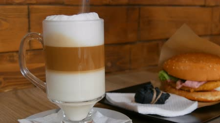 laktóz : Delicious freshly made latte on a table in a cafe. Latte coffee milk foam in transparent long special glass. Sugar sprinkles in drink. In background is delicious hamburger with lettuce, meat cutlet