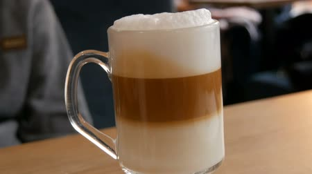 tartó : Delicious freshly made latte on a table in a cafe. Latte coffee milk foam in a transparent long special glass.